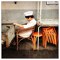 A cook takes a rest and uses his cellphone in the hutongs of central Beijing.
