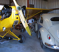 Pilot and aicraft mechanic Rich Kreloff's completely restored Piper J3 Cub and  completely restored VW Beetle in one of his hangars at the Petaluma Municipal Airport, Petaluma, Sonoma County, California.