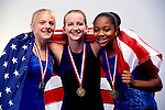 portrait of three teenage girl gymnasts draped with American flag