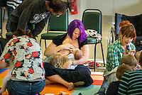 """A woman's husband looks on while his wife breastfeeds their newly arrived baby and an older toddler in tandem at a singing and signing group.Image from the breastfeeding collection of the """"We Do It In Public"""" documentary photography picture library project: <br />  www.breastfeedinginpublic.co.uk<br /> <br /> <br /> Berkshire, England, UK<br /> 27/09/2013<br /> <br /> © Paul Carter / wdiip.co.uk"""