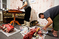 Filip Andreev (70) and his wife Angelina Andreeva (68) butcher a reindeer, killed in the Arctic tundra in Russia's far north, in the living room of their apartment in Naryan-Mar. As they work their dog chews a bone. /Felix Features