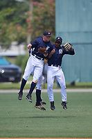 GCL Tigers East center fielder Kingston Liniak (15) celebrates with left fielder Matthew Jarecki (27) and right fielder Teddy Hoffman (17) after the final out of a game against the GCL Tigers West on August 8, 2018 at Tigertown in Lakeland, Florida.  GCL Tigers East defeated GCL Tigers West 3-1.  (Mike Janes/Four Seam Images)
