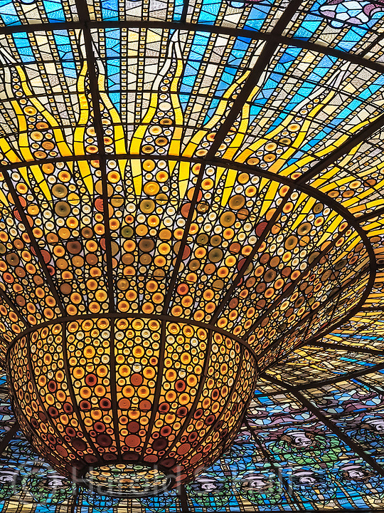 This is the famed Barcelona music hall, the Palau de la Música Catalana.  It is still a functioning concert holding many performances throughout any week in its 2,100 seat theater.  The unique characteristic of this privately owned music hall is the skylight in the center of the theater seating area.  This view is looking out from the third floor.