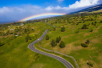 A bright rainbow over a winding road through Ulupalakua Ranch, Maui.