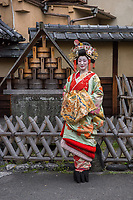 """Japan; Kyoto. Kikugawa, a Tayu or Oiran. Once known as a courtesans, they are highly educated in tea cermony, flower arranging, playing music, calligraphy, are well read and good conversationists. Her black teeth are a sign of beauty. Therare about 5 tayu today, compared to about 300 geisha. """"A tayu is my ideal woman image, I chose to be one. I was also concerned that this culture would disappear."""" Tayu walking down the street. Model released."""
