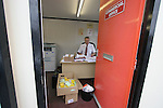 The commercial manager at Morecambe Football Club working at his desk in a portacabin in the car park. The club was preparing for the club's first-ever season in the Football League having been promoted from the Conference the previous season.  Photo by Colin McPherson.
