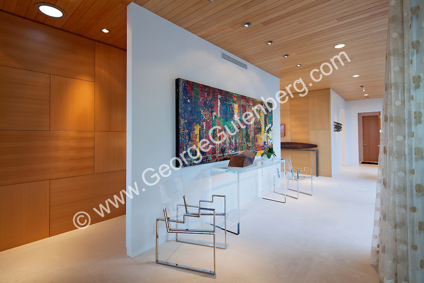 Beautiful woodwork is seen on walls in hallway with art