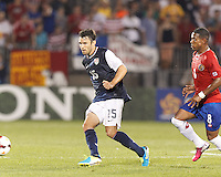 USMNT defender Michael Parkhurst (15) passes the ball as Costa Rican midfielder Kenny Cunningham (8) closes. In CONCACAF Gold Cup Group Stage, the U.S. Men's National Team (USMNT) (blue/white) defeated Costa Rica (red/blue), 1-0, at Rentschler Field, East Hartford, CT on July 16, 2013.