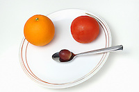Plate and spoon with one Orange, one tomatoe, one grape, on white background