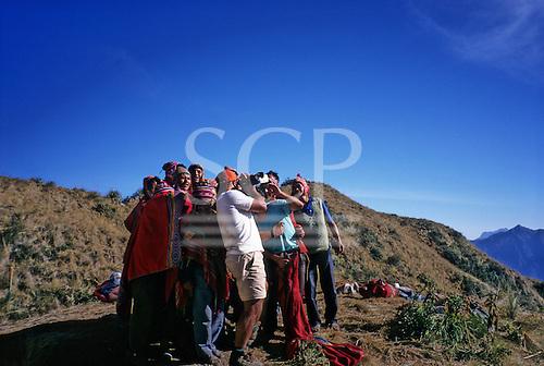 Inca Trail, Peru. Group of porters gathers around to watch playback on tourist videocamera at Phuyupatamarca campsite.