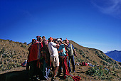 Inca Trail, Peru. Group of porters gathers around to watch playback on tourist videocamera at Phuyupatamarca campsite.