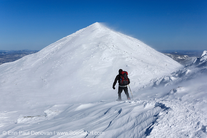 A winter hiker traveling north on the Appalachian Trail (Gulfside Trail) in extreme weather conditions in the New Hampshire White Mountains during the winter months. Mount Madison, the northernmost peak in the Presidential Range, is in the background.