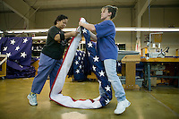 21 June 2005 - Oaks, PA - Estrellita Harris (L) and Nancy Rotay (R) fold a completed American flag at the Annin & Co. flag manufacturing plant in Oaks, PA. Photo Credit: David Brabyn.