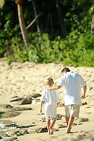 Father and son walking the beach while on vacation in Hawaii