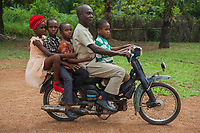 Nigeria. Abakaliki State. Uburu Amach. St. Patrick's Catholic Church. An Igbo family (father and four children) ride a motorcycle before the beginning of the religious service.The oldest daughter wears a head tie which is a women's cloth head scarf. The head tie is used as an ornamental head covering or fashion accessory, or for functionality in different settings. Its use or meaning can vary depending on the country and/or religion of those who wear it. The head tie is called gele in Nigeria. The family comes for the mass celebration for the 25th Priesthood Anniversary of Reverend Father Edward Inyanwachi. 14.07.19 © 2019 Didier Ruef