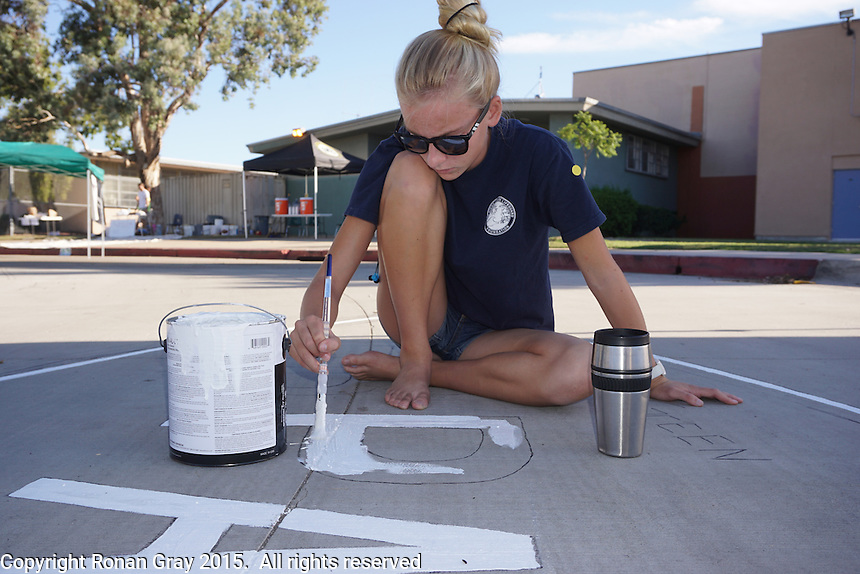 Mission Bay High School, San Diego CA, USA.  Saturday, October 10th 2015:  Mission Bay High School student Ciara Gray paints a mural that she designed in front of the High School Gym.  The mural was painted by students, staff and community members with funding for the installation provided by the non-profit organization Beautiful PB throgh a grant from SANDAG.