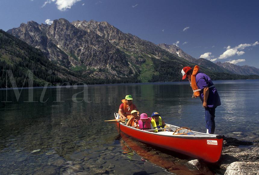 AJ3577, canoe, Grand Teton National Park, Lake Jenny, Grand Teton, Grand Teton Mountain, Wyoming, Rocky Mountains, A family wearing lifejackets gets ready to paddle their red canoe on Lake Jenny in Grand Teton National Park in the state of Wyoming.