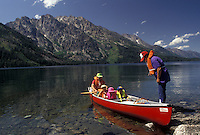 AJ3577, canoe, Grand Teton National Park, Lake Jenny, Grand Teton, Grand Teton Mountain, Wyoming, Rocky Mountains, A family wearing lifejackets gets ready to paddle their red canoe on Lake Jenny in Grand Teton National Park in the state of Wyoming.