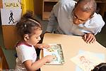 Education preschool 3-4 year olds male teacher talking with girl reading board book, she wears a  hearing aid