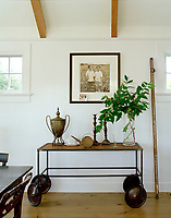 A vintage industrial trolley is transformed into a keeper of treasures in a between-window space at Victoria Hagan's Montauk beach retreat.
