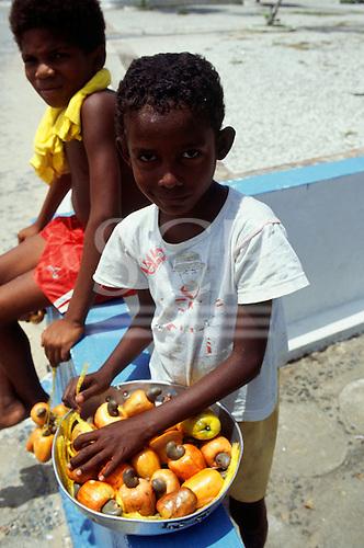 Itaparica Island, Brazil. Young boy selling whole cashew fruits (Anacardium occidentale). Bahia State.