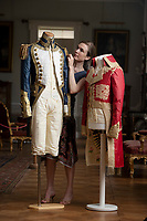 BNPS.co.uk (01202) 558833<br /> Pic: ZacharyCulpin/BNPS<br /> <br /> Pictured: Artist Stephanie Smart with the incredible paper outfits. (From left) An early 19th century British naval uniform and a coat inspired by Napoleon.<br /> <br /> A textile artist has unveiled a collection of remarkable Regency outfits she has painstakingly made out of paper.<br /> <br /> Stephanie Smart has produced 11 life-sized outfits including a red frockcoat modelled on the style of Napoleon.<br /> <br /> Others depict walking dresses, naval uniforms and spencer jackets from the Regency era. (1795-1837)<br /> <br /> Her creations are on display as part of an exhibition titled The Regency Wardrobe at Firlie Place in East Sussex.