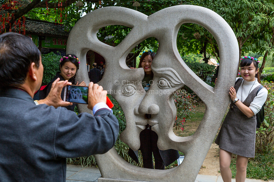 Guilin, China.  Elephant Trunk Hill Park.  Man Taking Picture of Three Women with Modern Sculpture Representing Love.
