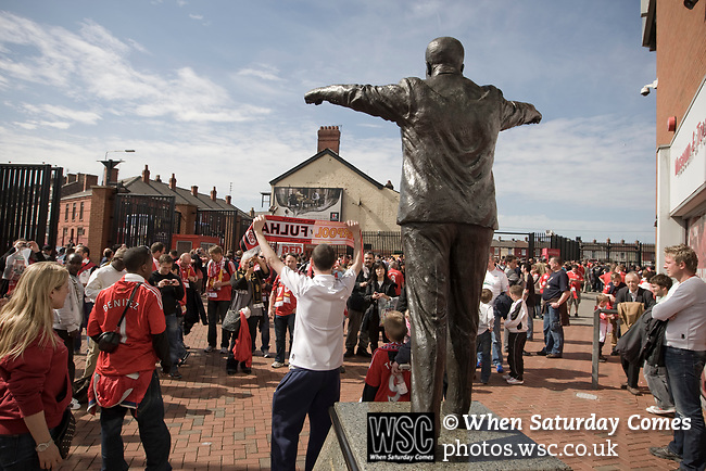 Fans looking at the statue of former Liverpool manager Bill Shankly outside Anfield, home of Liverpool football club, pictured before the club took on Fulham in a Premier League match during the 2009-10 season. The club was one of the most successful and best supported teams in England and which won many domestic and European trophies. The most-famous part of the stadium was the Kop, where the Liverpool fans sat during games. Photo by Colin McPherson