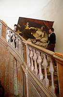 Curators carry a painting up a wooden staircase