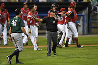 Umpire J.C. Velez gets in between the Batavia Muckdogs and Jamestown Jammers after the benches cleared when Victor Castro (not shown) was hit by a pitch on July 25, 2014 at Dwyer Stadium in Batavia, New York.  Batavia defeated Jamestown 7-2.  (Mike Janes/Four Seam Images)