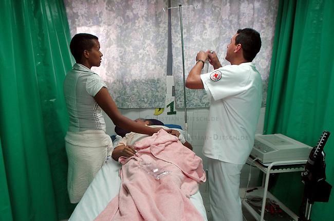 """Programm Barrio Adentro in Venezuela<br /> Mit dem sog. Programm Barrio Adentro versucht die Regierung des venezuelanischen Praesidenten Chavez die Gesundheitsversorgung, die Bildung und Lebensmittelversorgung in sozial benachteiligten Gebieten herzustellen. Es wurden u.a. Hospitales Pupular (Volkskrankenhaeuser) und Polikliniken errichtet, in denen z.B. die Gesundheitsversorgung für alle in den jeweiligen Stadtbezirk lebenden Menschen kostenlos ist.<br /> Organisiert werden die einzelnen Projekte (span. Modules) von den Volks-Versammlungen in den Bezirken und nicht zentral von der Regierung. Diese stellt nur die noetigen Mittel zur Verfuegung.<br /> Hier: Ein Arzt in der """"Clinica Popular"""" im Armenbezirk Caricuao legt eine Infusion fuer eine zuckerkranke Frau.<br /> 6.11.2004, Caracas / Venezuela<br /> Copyright: Christian-Ditsch.de<br /> [Inhaltsveraendernde Manipulation des Fotos nur nach ausdruecklicher Genehmigung des Fotografen. Vereinbarungen ueber Abtretung von Persoenlichkeitsrechten/Model Release der abgebildeten Person/Personen liegen nicht vor. NO MODEL RELEASE! Nur fuer Redaktionelle Zwecke. Don't publish without copyright Christian-Ditsch.de, Veroeffentlichung nur mit Fotografennennung, sowie gegen Honorar, MwSt. und Beleg. Konto: I N G - D i B a, IBAN DE58500105175400192269, BIC INGDDEFFXXX, Kontakt: post@christian-ditsch.de<br /> Bei der Bearbeitung der Dateiinformationen darf die Urheberkennzeichnung in den EXIF- und  IPTC-Daten nicht entfernt werden, diese sind in digitalen Medien nach §95c UrhG rechtlich geschuetzt. Der Urhebervermerk wird gemaess §13 UrhG verlangt.]"""