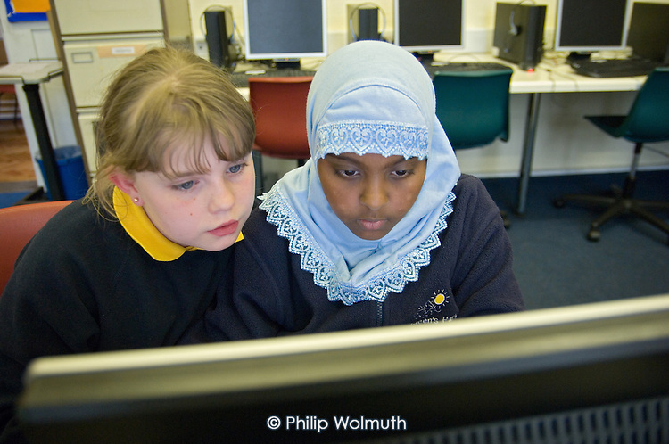 Year 5 and 6 pupils learn to access the internet at a Homework Club at Queens Park Primary School, West London.