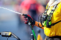 Aug 8, 2020; Clermont, Indiana, USA; Detailed view as an NHRA official uses a water hose to spray water in the burnout box during qualifying for the Indy Nationals at Lucas Oil Raceway. Mandatory Credit: Mark J. Rebilas-USA TODAY Sports