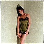 Woman wearing negligee against green patterned wallpaper background