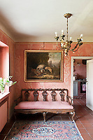 In the entrance hall, an antique 18th century Venetian sofa sits against a hand-painted wall, decorated by the owner with a Fortuny motif