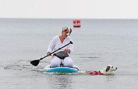 """BNPS.co.uk (01202 558833)<br /> Pic: ZacharyCulpin/BNPS<br /> <br /> Pictured: Lizzie Wilkkinson with her Springer-Collie called """"Diogie"""" who decided to swim the last few metres<br /> <br /> Putting their best paw forward hoping to ride the wave of success - Competitors and their dogs take part in the annual Dog Surfing championships. <br /> <br /> The event known as The 'dogmasters' took place today on Bournemouth beach in front of packed crowd, it's the country's only dog surfing and paddleboard championship."""