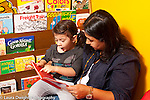 Toddler program female teacher looking at book with girl who is pointing at picture and talking