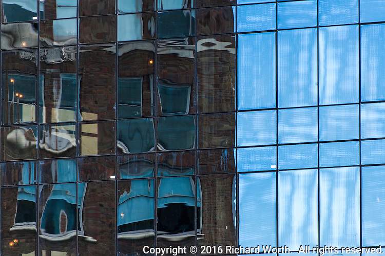 Window panes reflect a nearby office building and the cloud streaked sky in downtown Oakland, California.