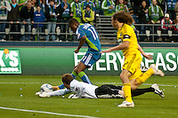 Steve Zakuani(l) of the Seattle Sounders scroes against Goalkeeper William Hesmer and Frankie Hejduk (r) of the Columbus Crew at the XBox 360 Pitch at Quest Field in Seattle, WA on May 1, 2010. the Sounders and Crew played to a 1-1 draw.