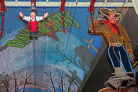 Las Vegas, Nevada.  Fremont Street.  Male Zip Line Rider on the Zoomline Approaching Cowboy Sign.