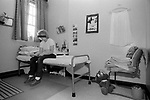 Woman in prison cell UK 1980s. Female prisoner in her own room sitting on bed reading letter.  HM Prison Styal Wilmslow Cheshire England 1986