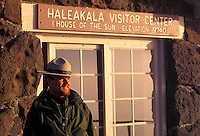 A Haleakala National park ranger stands next to the Haleakala Visitor Center sign after sunrise.