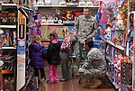 Nevada National Guard Sgts. Michael Wazelle, rear, and Tim Stephenson shop with local students at the 10th annual Holiday with a Hero event at Walmart in Carson City, Nev., on Wednesday, Dec. 17, 2014. The event pairs 200 of Carson City's K-5th grade homeless students with a local heroes for Christmas shopping. <br /> Photo by Cathleen Allison