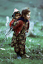 Irak 1973.Petite fille avec son frère sur le dos.Iraq 1973.Young girl carrying her brother.