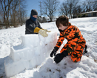 William Brazell, 14, (left) and his brother, Ryan Brazell, work together Tuesday, Feb. 16, 2021, to make an igloo using a storage container to shape bricks from snow in front of their house in Greenland. The two were reminded of an igloo that their father made years ago and wanted to recreate it. Visit nwaonline.com/210217Daily/ for today's photo gallery. <br /> (NWA Democrat-Gazette/Andy Shupe)