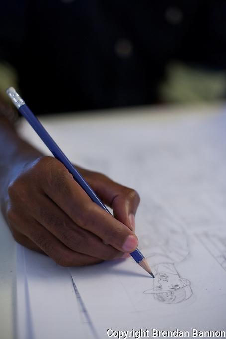 Eric Muthoga, Shujaaz FM comic book line artist drawing a character.