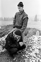 Two Bosnian men grieve at a friend's grave in a makeshift cemetery in a soccer field in Sarajevo on December 10, 1993.
