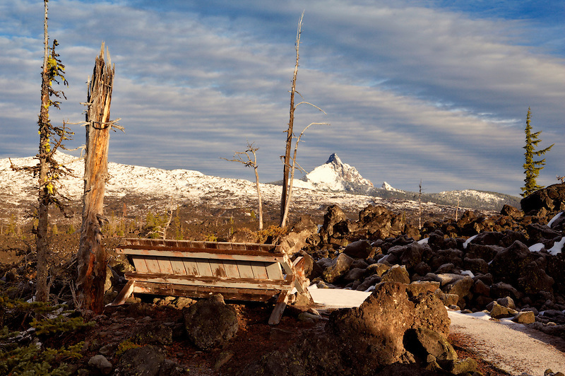 Bench on trail at Dee Wright Observatory with Mt. Washington. Central Oregon