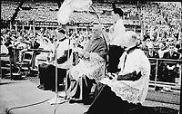le Congrès des cent mariés au stade De Lorimier à Montréal. Ce second congrès organisé par le Mouvement des Jeunesses ouvrières catholiques (J.O.C.) constituait l'aboutissement de deux années d'enquête sur la situation des jeunes, en regard de la préparation au mariage et de l'étude de l'encyclique du Pape Pie XII sur le mariage.<br /> <br /> Lors de ces noces collectives, 105 jeunes couples se sont mariés entourés par une haie de jocistes (membres des J.O.C.) En tout 525 personnes; époux et témoins devaient signer les registres d'état civil et religieux. Six évêques, en compagnie de Mgr Gauthier, archevêque de Montréal et Mgr Albert Sanschagrin, responsable du congrès officiaient au micro cette cérémonie pour les jeunes mariés rassemblés devant une foule d'environ 25 000 spectateurs.<br /> <br /> PHOTO : Conrad poirier - BANQ