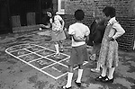 Junior school children playing in the playground Hopscotch games. South London. 1970s England. Mixed ethnic group of girls, BAME black British and white kids. 1975 UK
